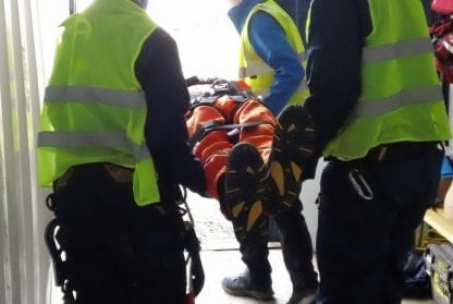 people carrying person on a stretcher